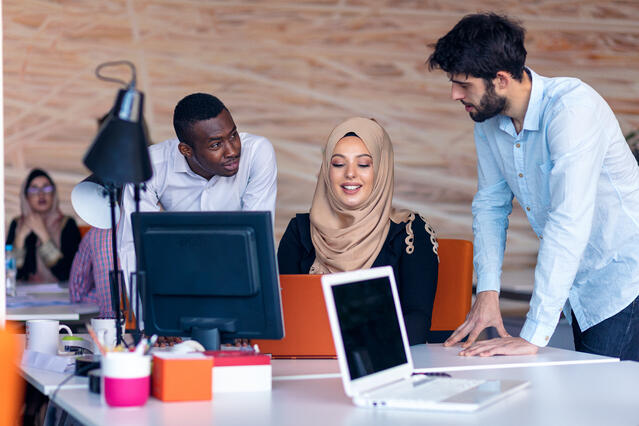 Three people discussing 4 ways to become more effectively assertive in the workplace